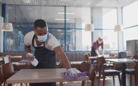 worker cleaning table with disinfectant in restaurant during coronavirus outbreak