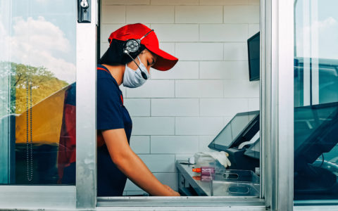 fast food cashier in drive thru service wearing hygiene face mask to protect coronavirus pandemic or covid-19 virus outbreak working on counter at the station.
