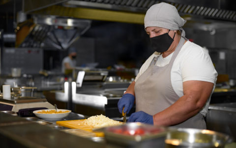 chef wearing protective black mask on her face while working in restaurant kitchen